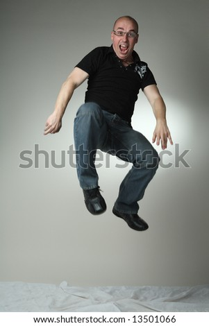Casual man jumping. Shot in studio. - stock photo