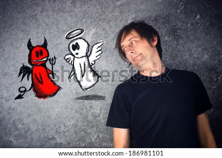 Casual man looking at doodle drawing of angel and devil fighting. Concept of conscience; decisions, uncertainty, moral dilemma; fight of good and evil.