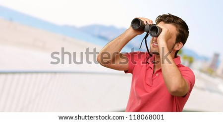 casual man looking into binocular, outdoor - stock photo