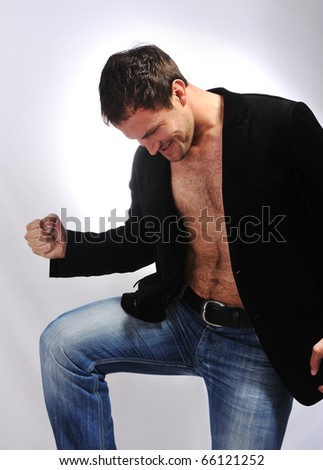 casual man looking very happy with his arm and leg up - stock photo