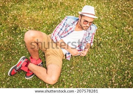 casual man lying down to his side and looks away, on a field - stock photo