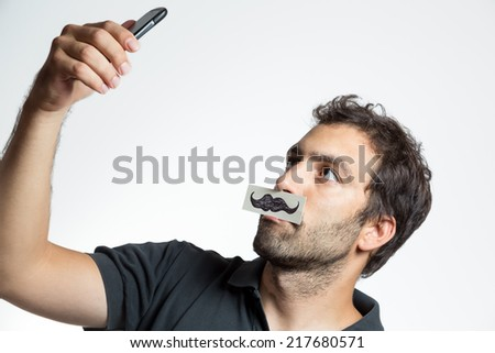 casual man make high view selfie portrait with fake moustache,  close composition isolated - stock photo