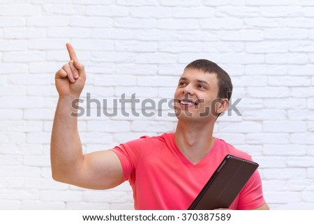 Casual Man Point Finger Up Copy Space Holding Tablet Computer Standing Over White Brick Wall - stock photo