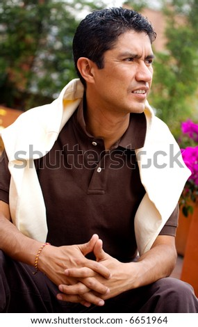 casual man portrait sitting down and looking pensive outdoors - stock photo