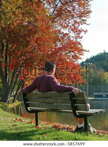 Casual man relaxing on park bench along pond with autumn trees - stock photo