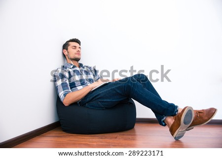 Casual man resting on the bag chair with headphones