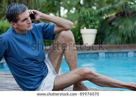 Casual man sitting near poolside talking on cell phone - stock photo