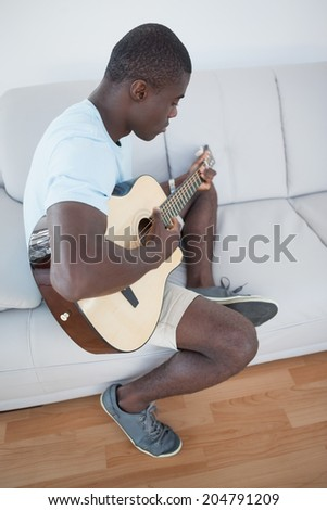 Casual man sitting on sofa playing the guitar at home in the living room