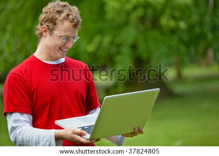 Casual man smiling and carrying a laptop outdoors