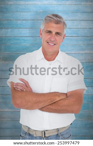 Casual man smiling at camera against wooden planks