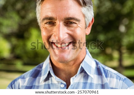 Casual man smiling at camera on a sunny day
