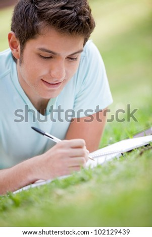 Casual man studying outdoors with a notebook - stock photo