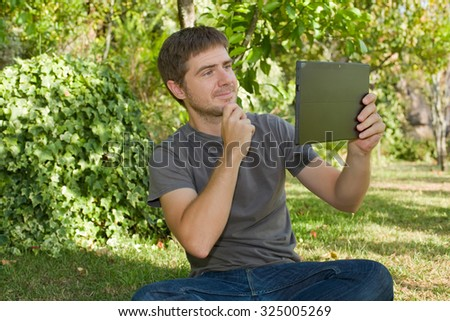 casual man taking a picture with a tablet pc, outdoor - stock photo