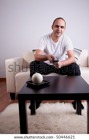 casual man watching tv on sofa - stock photo