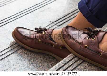Casual man wear brown leather shoes sitting at staircase in the afternoon. - stock photo