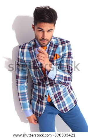casual man wearing plaid jacket posing in studio background while pointing up and looking at the camera  - stock photo