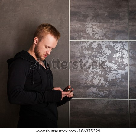 Casual man with touch screen phone near the grey wall - stock photo