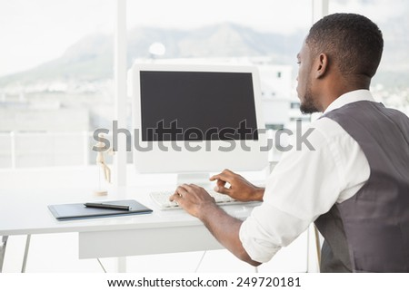 Casual man working at desk with computer and digitizer in his office - stock photo