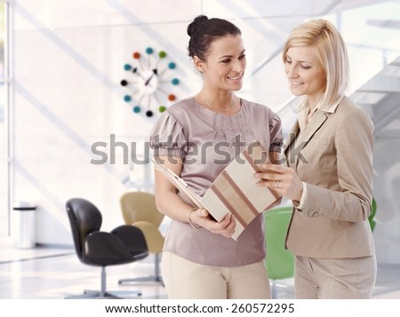 Casual mid adult attractive caucasian businesswomen working at bright business office with report folder in hand. Smiling, standing, satisfied. Copy space. - stock photo