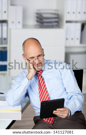 Casual mid age man looking at his tablet inside the office - stock photo