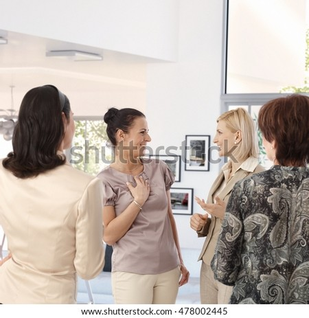 Casual middle aged, caucasian businesswoman meeting colleagues at home. Relaxed, happy, smiling, chatting about business, standing, gesturing, group of people.