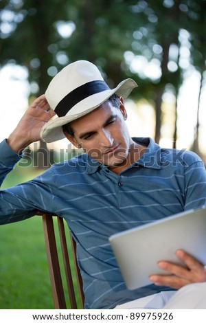 Casual middle aged man looking at tablet PC screen - stock photo