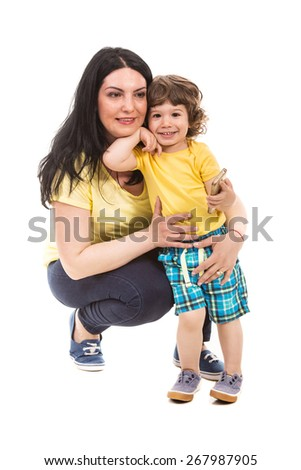 Casual mother and toddler son posing and the boy holding phone mobile isolated on white background