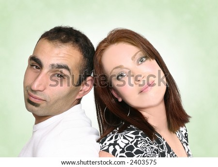 Casual multicultural couple leaning against each other and looking ahead - green background. - stock photo