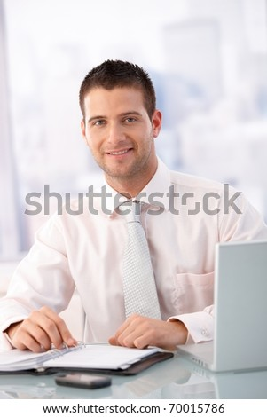 Casual office worker sitting at desk in office, smiling.? - stock photo