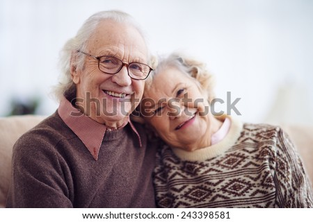 Casual pensioners looking at camera with smiles - stock photo