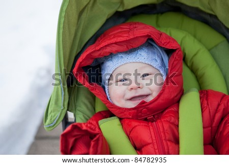 Casual portrait of a smiling baby in a stroller on a snowy winter day - stock photo