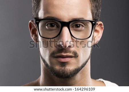 Casual portrait of a young man wearing nerd glasses, over a gray background - stock photo