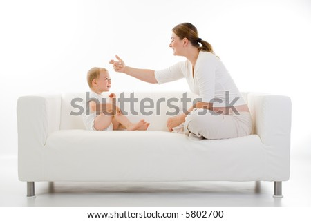Casual portrait of a young mother and toddler sitting on a white couch facing each other and interacting. - stock photo