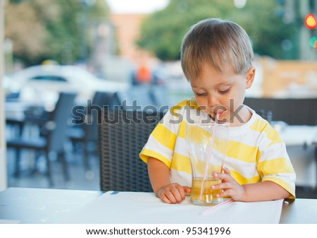 Casual portrait of adorable little boy drinking juice in outdoor restaurant