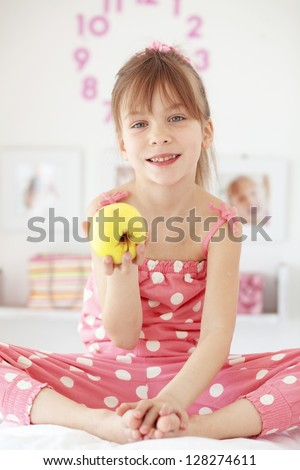 Casual portrait of cute child eating apple in bed - stock photo