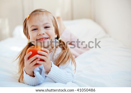 Casual portrait of cute child with apple in bed - stock photo