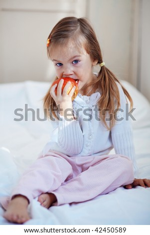 Casual portrait of cute child with apple in bed
