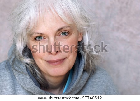 Casual portrait of happy mature woman with natural white hair and minimal makeup. - stock photo