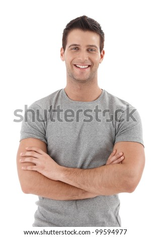 Casual portrait of happy university student guy standing with arms folded, laughing.
