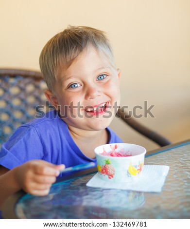Casual portrait of little boy eating ice cream in cafe - stock photo