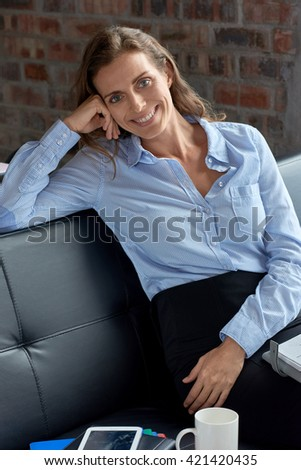 Casual portrait of relaxed business woman sitting on couch - stock photo