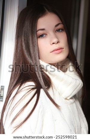 Casual portrait of young beautiful girl in white pullover - stock photo
