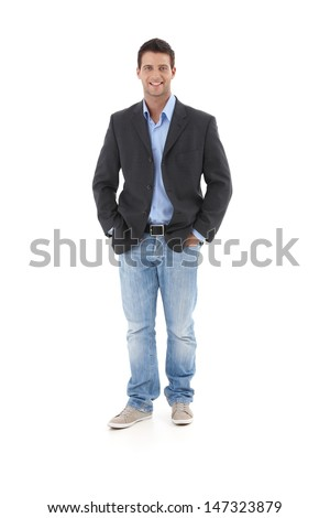 Casual portrait of young businessman, standing with hands in pocket, smiling at camera, isolated on white. - stock photo