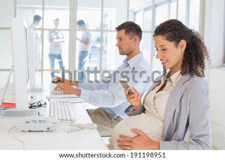 Casual pregnant businesswoman texting on phone at desk in the office - stock photo