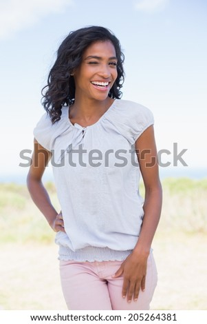 Casual pretty woman smiling at camera on a sunny day in the countryside - stock photo