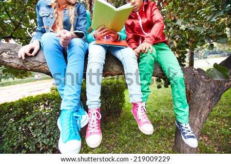 Casual schoolkids sitting on tree branch and reading - stock photo