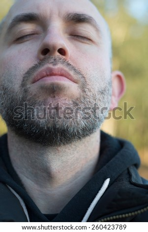 Casual sefie portrait of a adult beard man in vertical composition. Man has his eyes closed. - stock photo