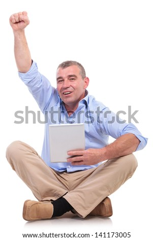 casual senior man sitting on the floor with his legs crossed and holding a tablet in his hand while cheering. isolated on white background - stock photo