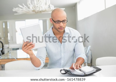Casual serious young man with digital tablet and diary at home - stock photo