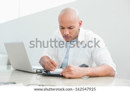 Casual serious young man with laptop writing in diary at home